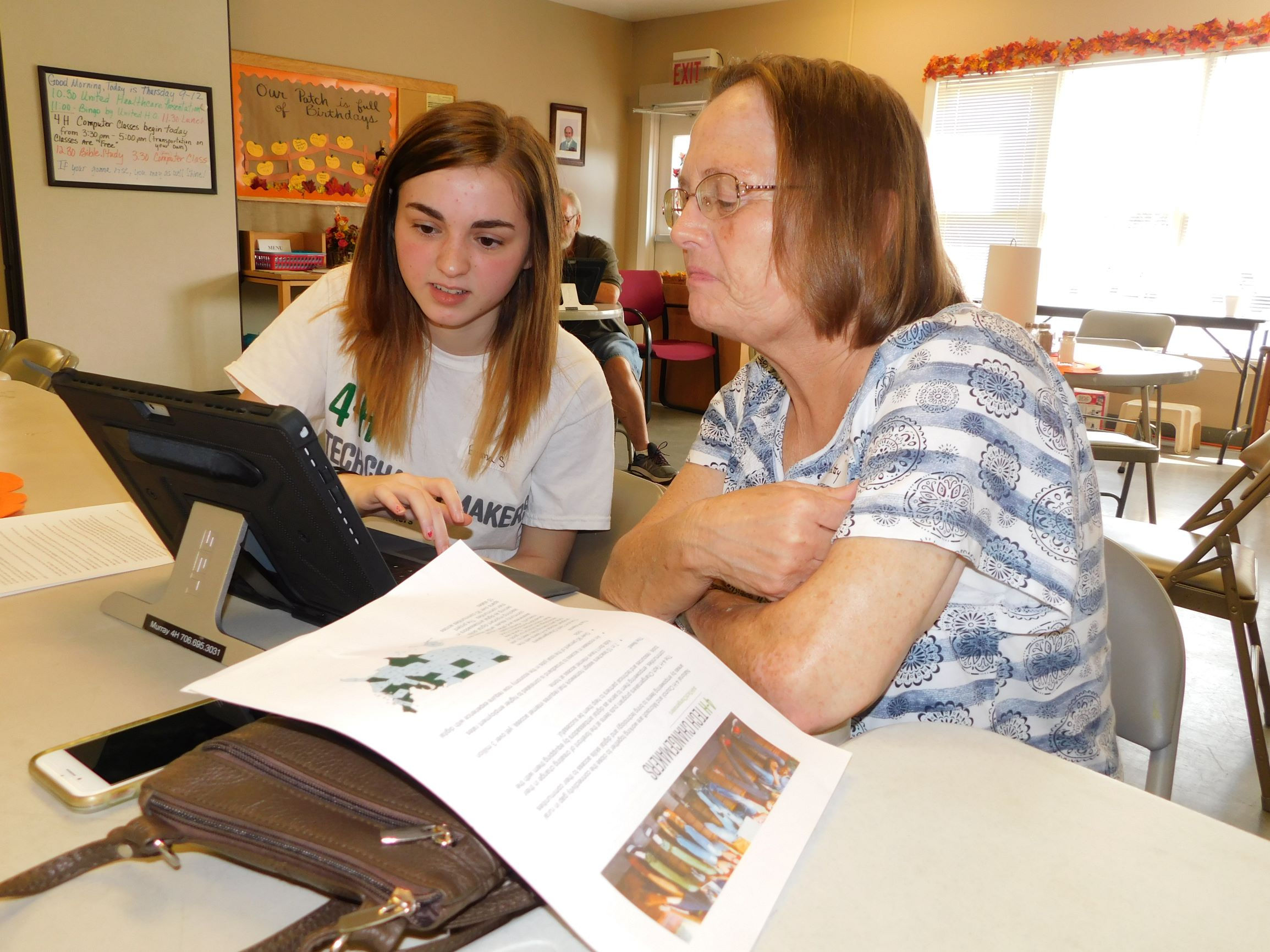 Tech Changemaker youth leader Emma works with her partner on a Microsoft Surface Pro during the monthly technology help session at the Murray County Senior Center.