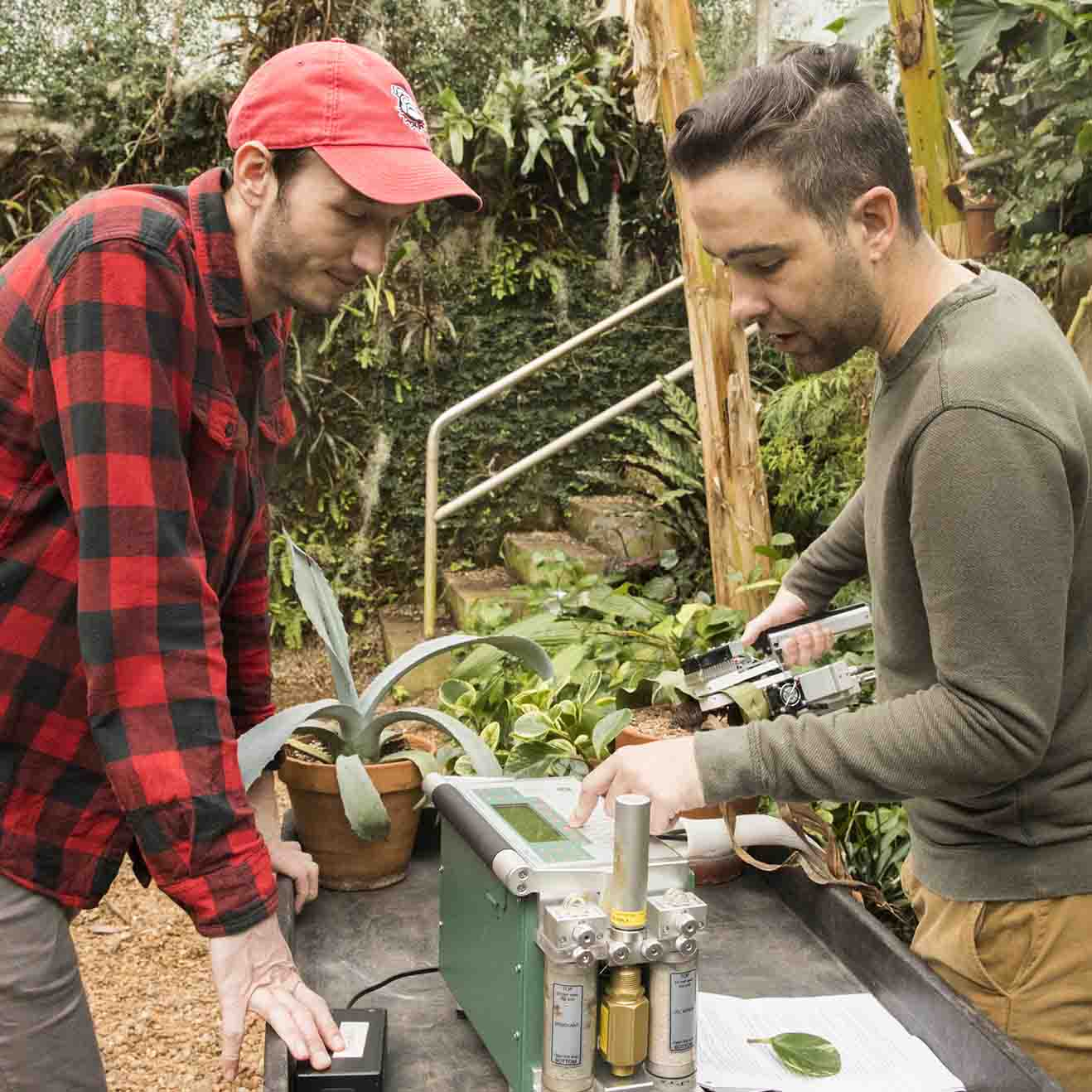 Graduate student Philip Bentz (left) and graduate student Rick Field (right) use a carbon dioxide sensor on a plant in the horticulture greenhouses. Bentz enrolled to UGA in the Integrated Plant Sciences program in 2019. (photo by Dorothy Kozlowski, taken prior to March 2020)