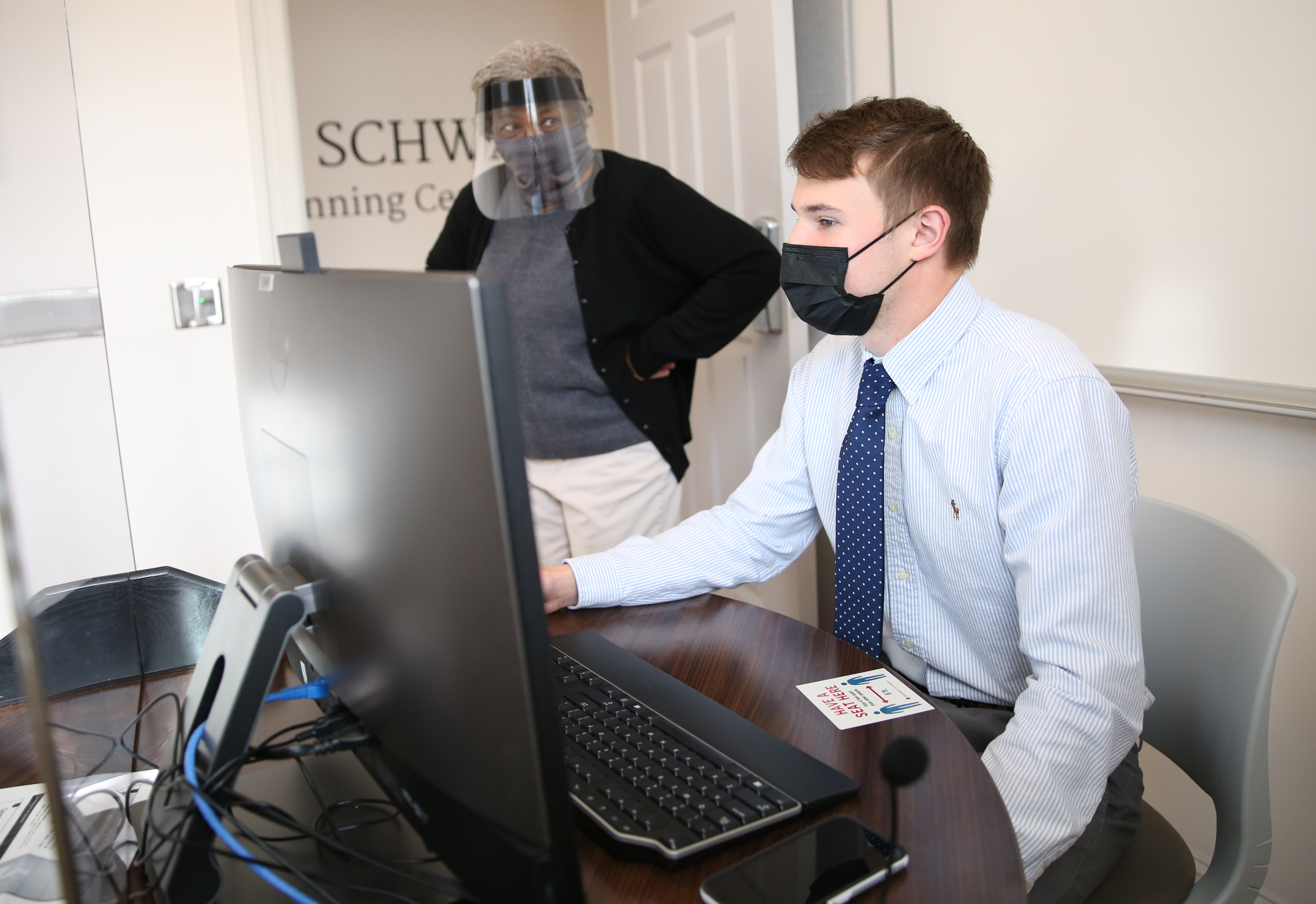 Blake Ertzberger, a financial planning major and student service provider in the UGA College of Family and Consumer Sciences, gets instruction from Joan Koonce, a FACS professor and UGA Extension financial planning specialist, as part of the VITA program at UGA.