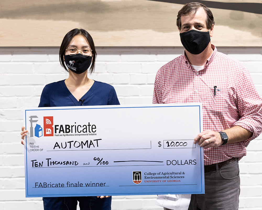 Greena Kim poses with Chris Rhodes, accepting the $10,000 grand prize.