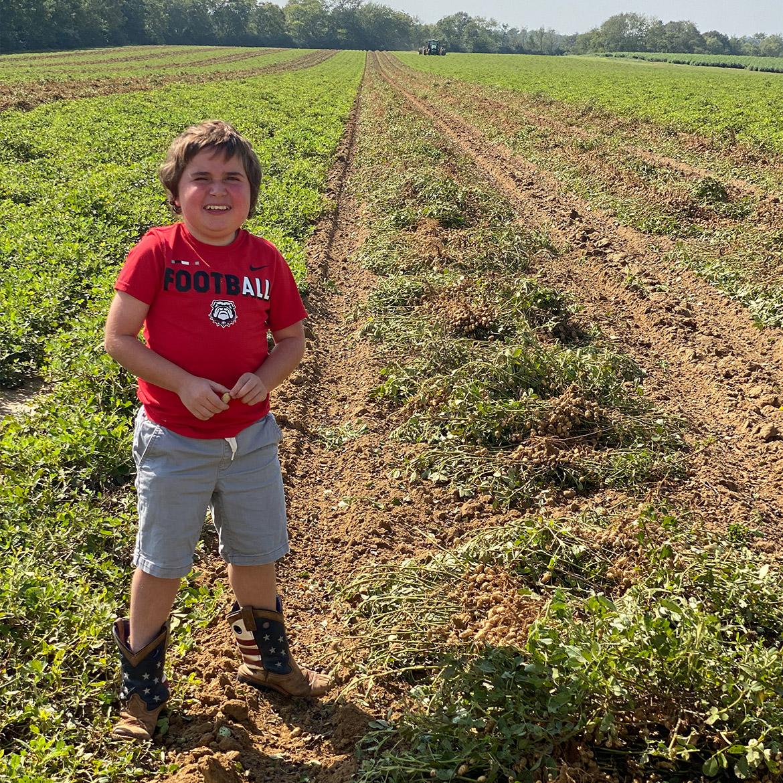 Wesley Cleveland为他最喜欢的T恤的一张照片姿势,站在收获期间的花生庄稼行之间。