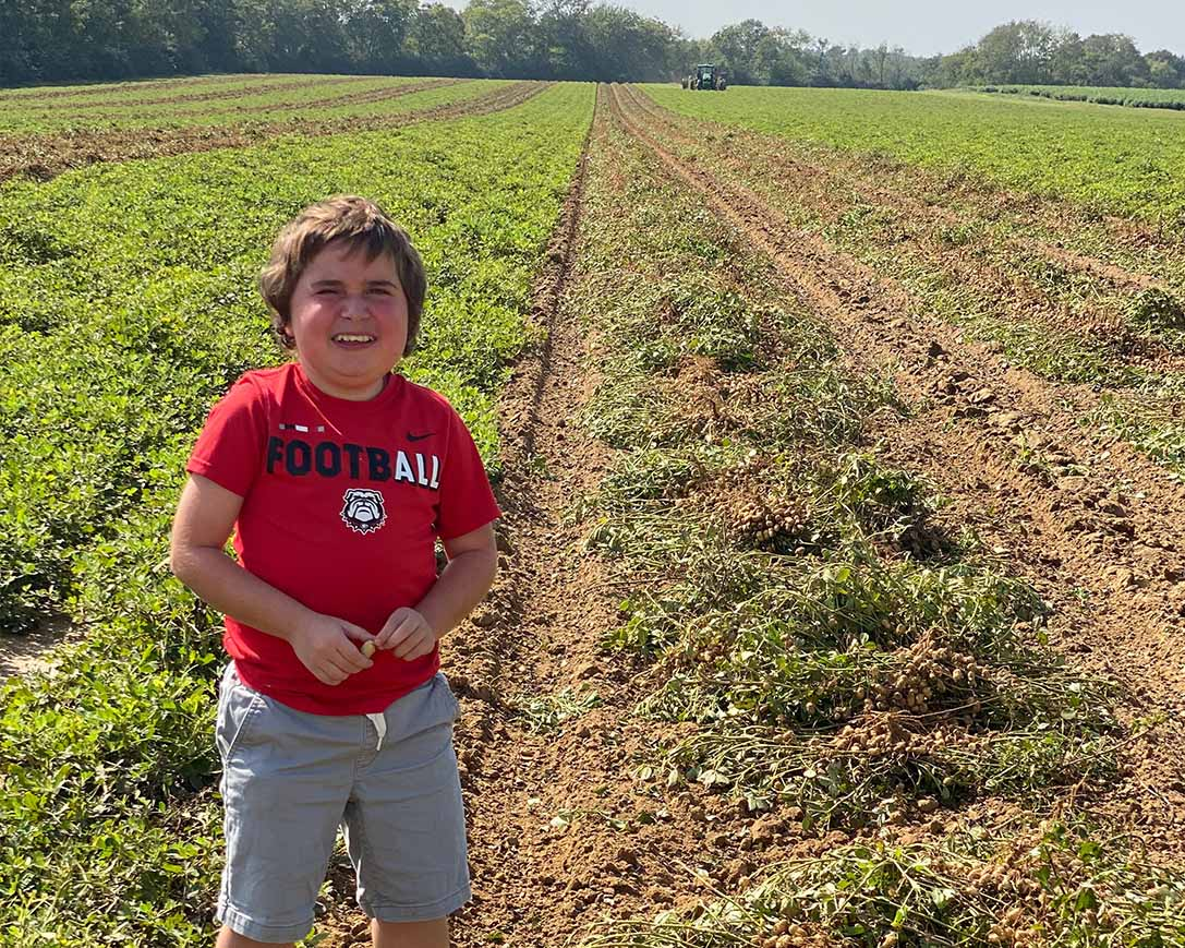 Wesley Cleveland poses for a photo in his favorite t-shirt, standing between rows of peanut crops during harvest.
