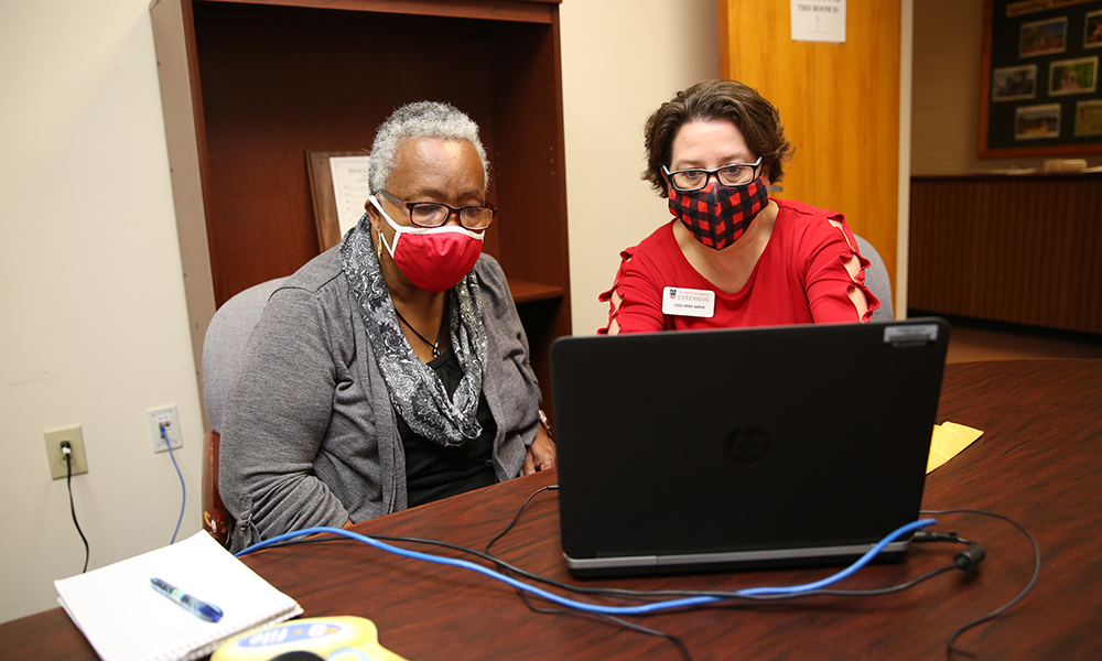 Leigh Anne Aaron (right), a UGA Cooperative Extension agent serving Morgan and Oconee counties, assists Oconee County resident Hallie Adams with tax preparation as part of the UGA Volunteer Income Tax Assistance Program.