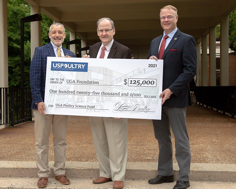 CAES Dean Nick Place (left) and Department of Poultry Science Head Todd Applegate (right) receive a pledge for student recruitment funding from USPOULTRY President John Starkey (center).