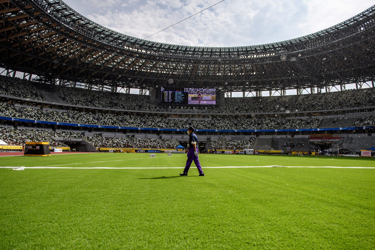 An official walks across the infield of the National Stadium in Tokyo, home of the 2020 Olympic Games. A UGA-bred grass will be used on the field. (Photo by PHILIP FONG/AFP via Getty Images)