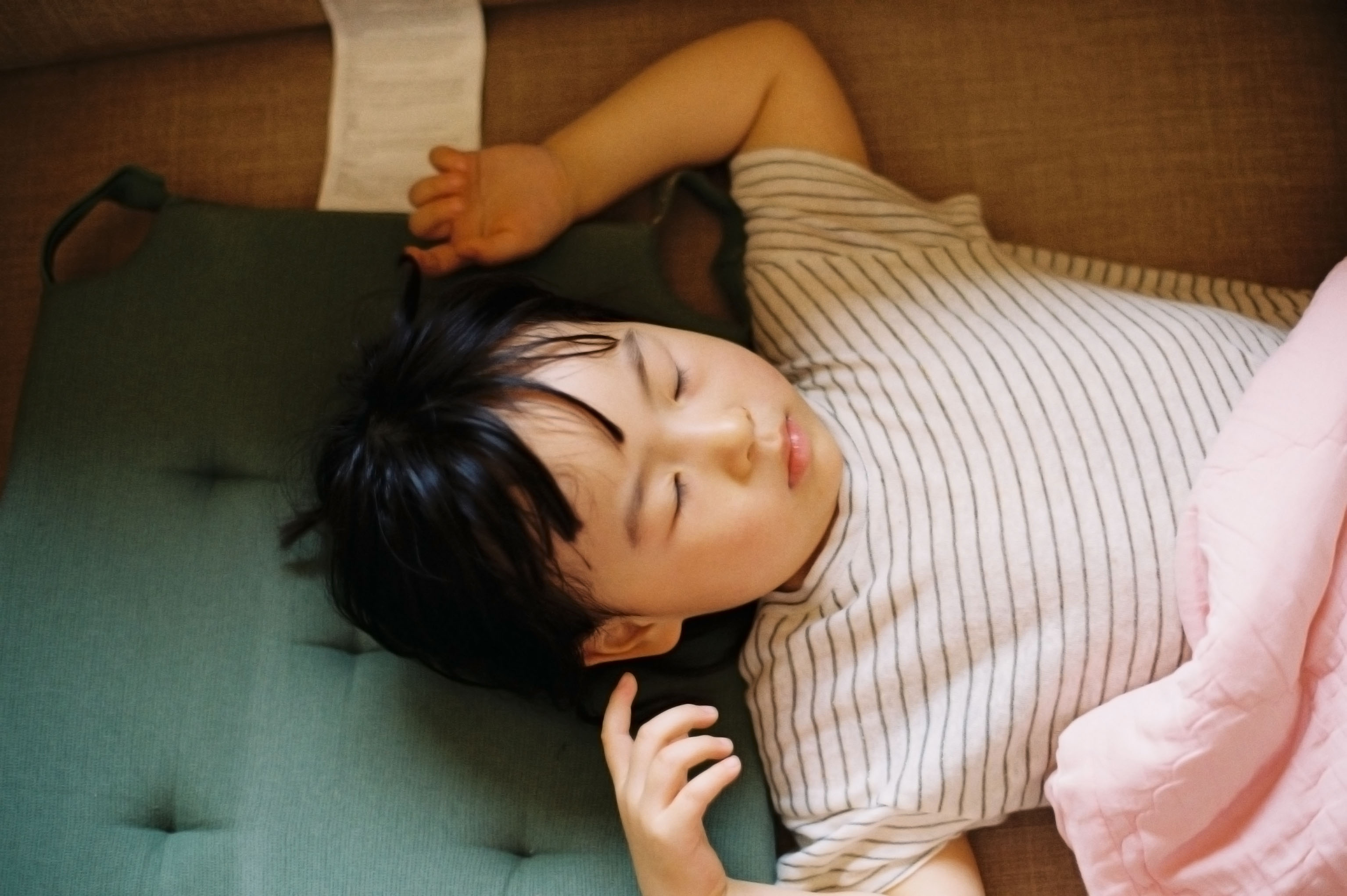 Child sleeps with his arms over his head