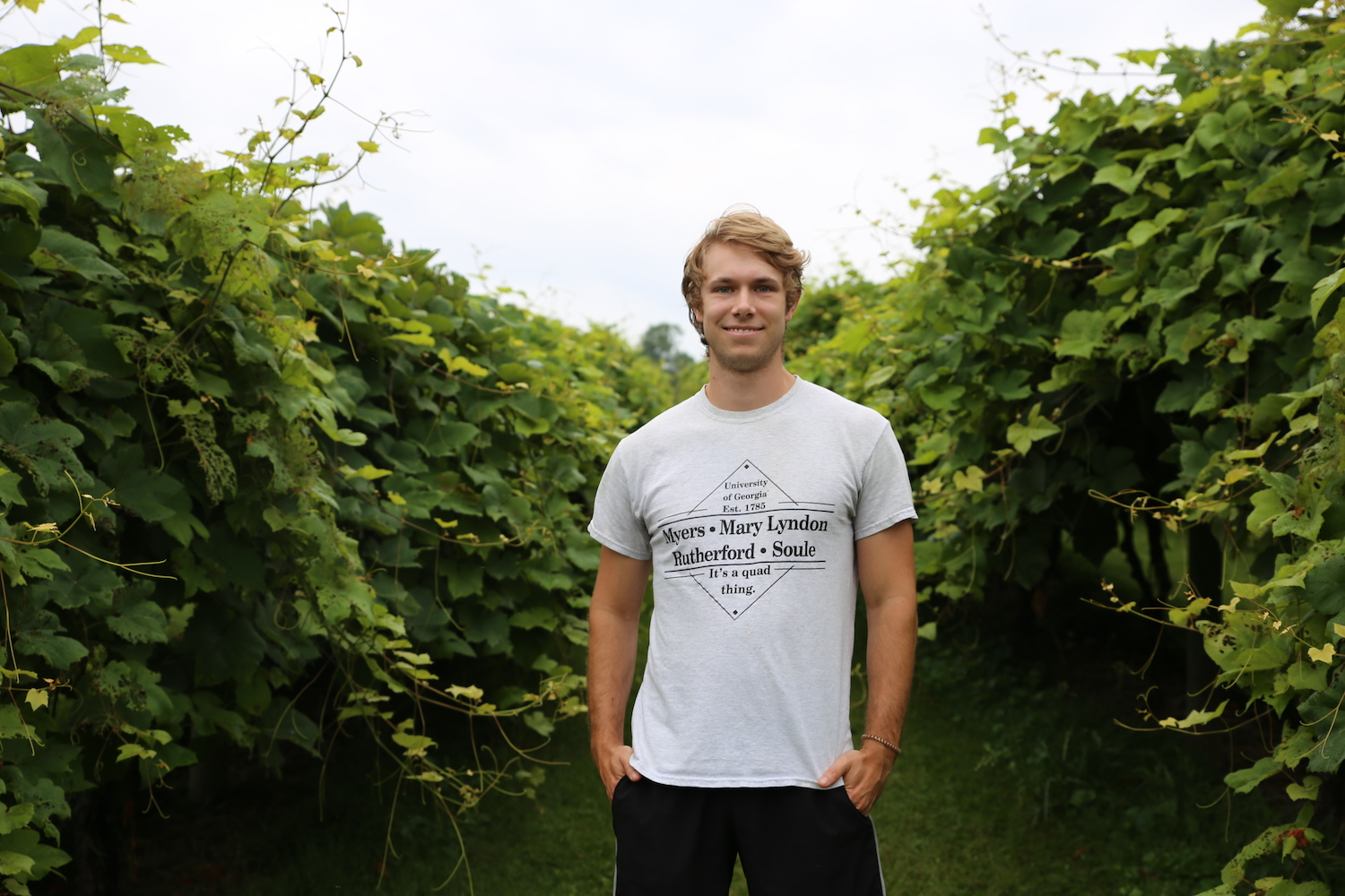 Trent Sutton stands in the foreground with vines at his back at Tiger Mountain Vineyards.