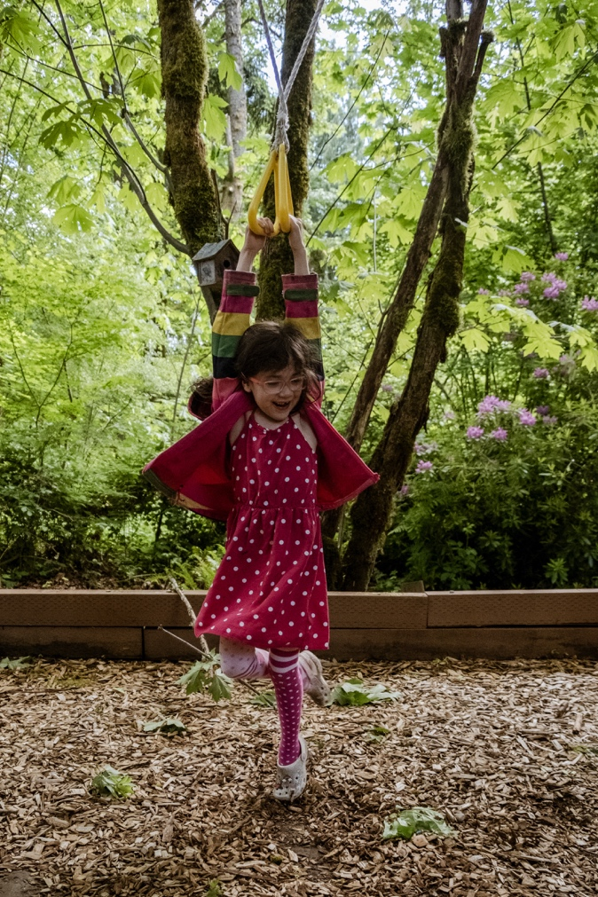 Young girl plays on a rope swing among trees