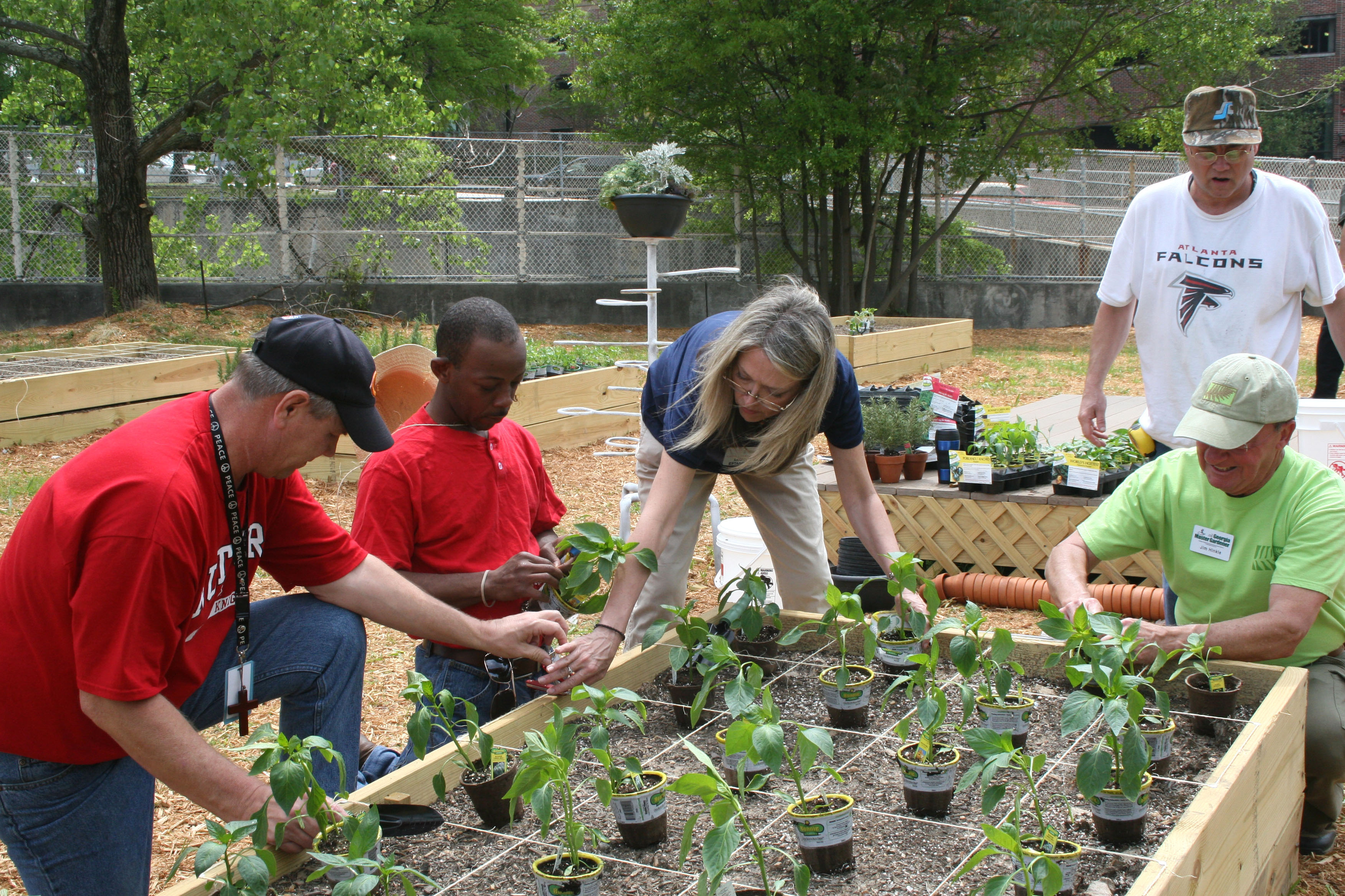 University of Georgia Cooperative Extension Agent Louise Estabrook (center) and UGA Master Gardener Jim Hinkle (far right) help residents at the Atlanta Mission install plants in the mission's garden.