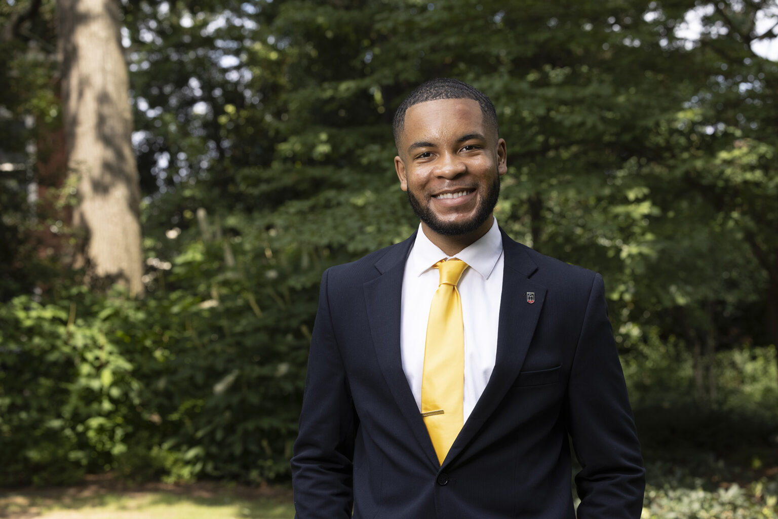 Eric Okanume, a Black student, smiles on campus in a dark suit with yellow tie and UGA pin.