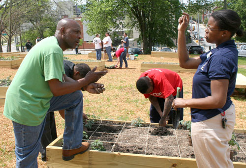 University of Georgia Fulton County Extension Agent Kisha Faulk answers questions from a resident of the Atlanta Mission during a work day at the mission's garden.
