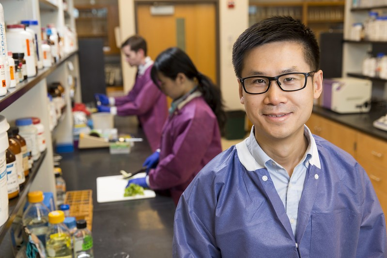 Xiangyu Deng smiles in front of two researchers working in the lab