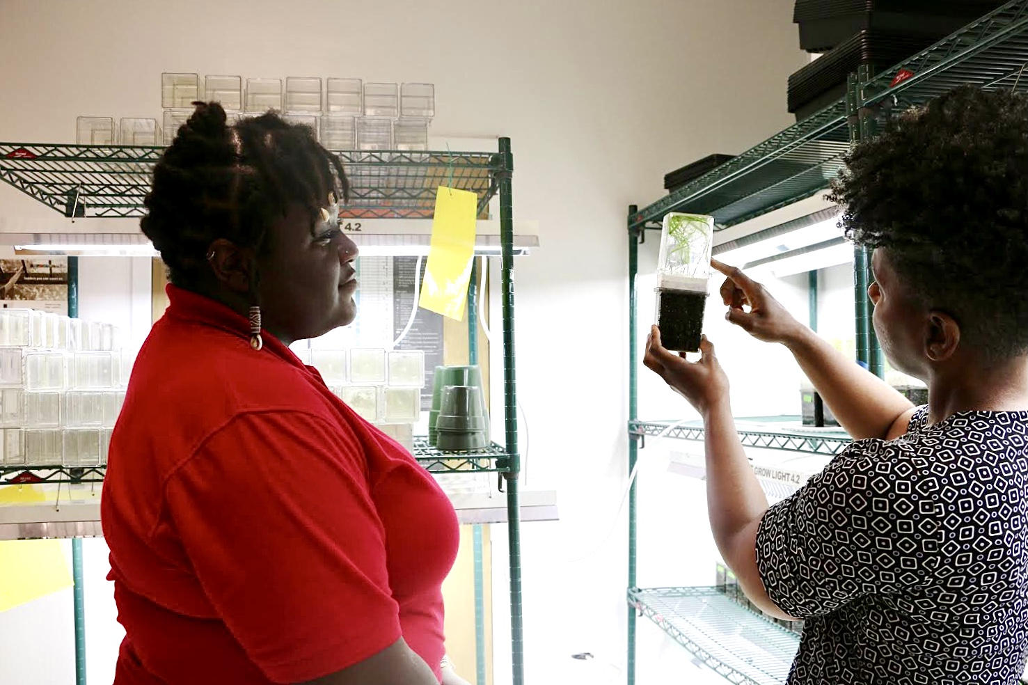 Shavannor Smith points to a plant specimen in the lab with graduate student Makayla Mitchell