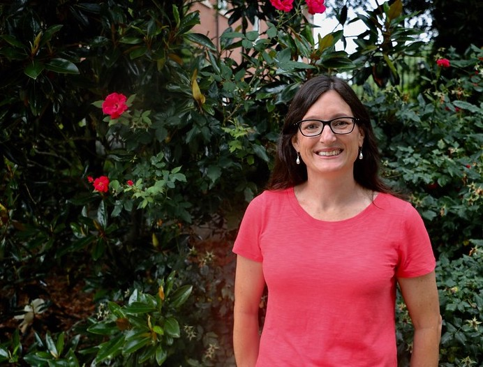 Professor Marin Brewer smiles in front of a flowering shrub on campus