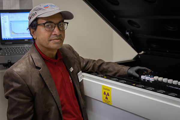 Uttam Saha displays radon samples in the AESL's liquid scintillation counter, which measures radioactivity in water samples.