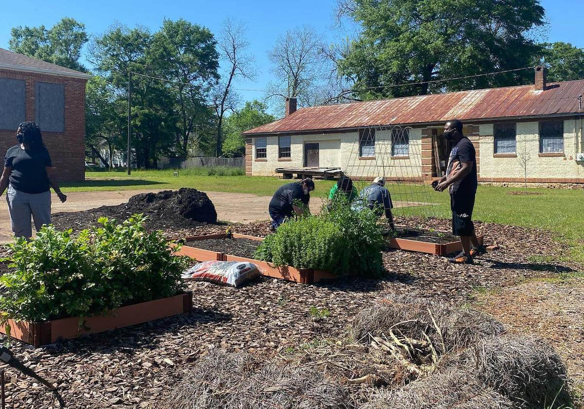 Community members work together to plant the Richland Community Garden, with blue skies and older buildings in the background.