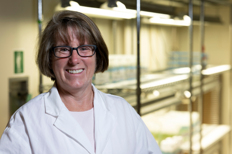Robin Buell smiles in her lab, wearing a white lab coat and glasses and standing in front of a set of shelves