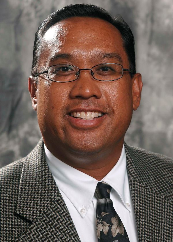 John Salazar, a man in a suit and glasses, smiles in his professional headshot
