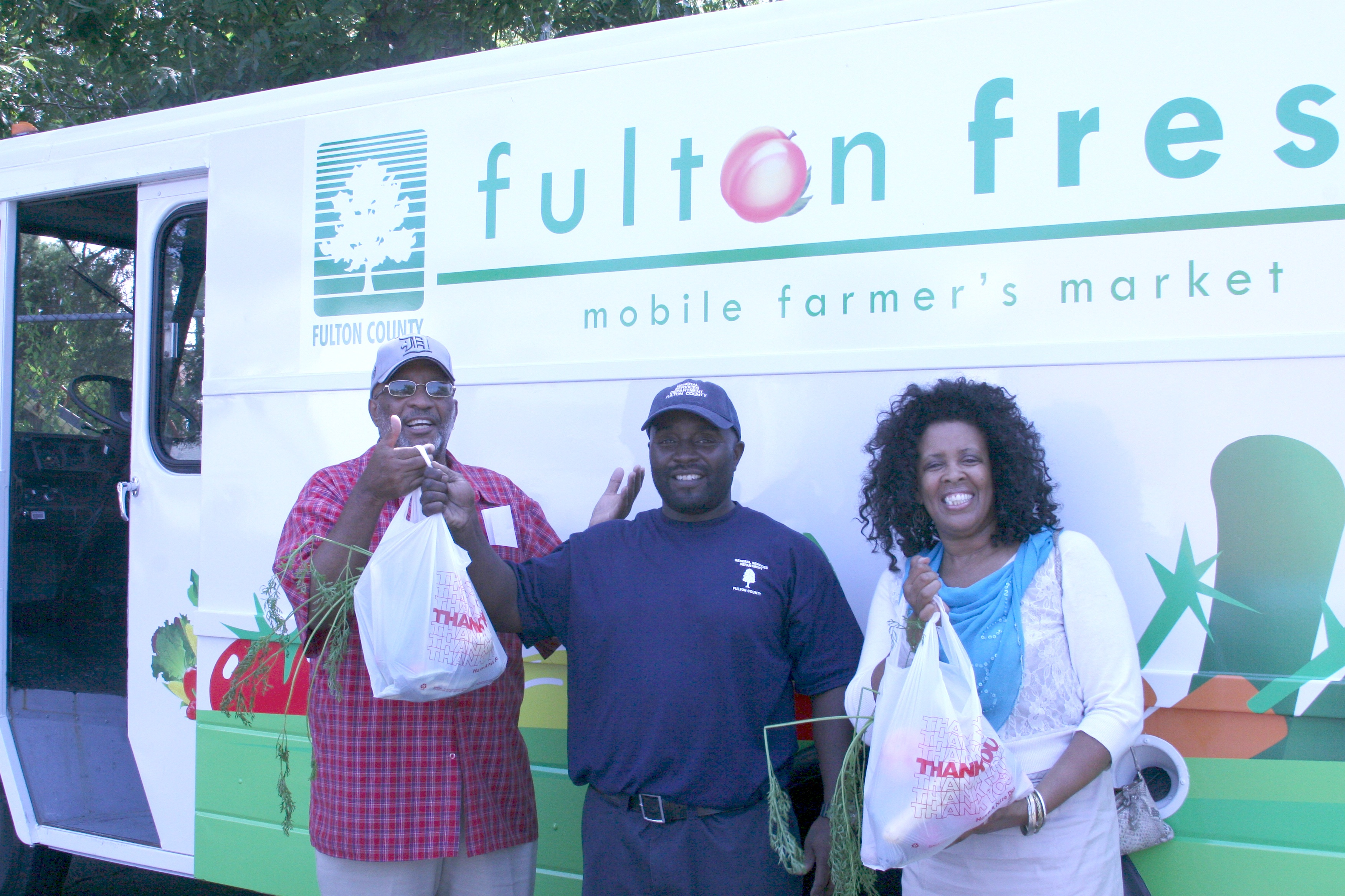 Fulton County employee Eric Johnson (center) hands free vegetables to Fulton County residents at a recent session of the Fulton Fresh Mobile Farmer's Market.