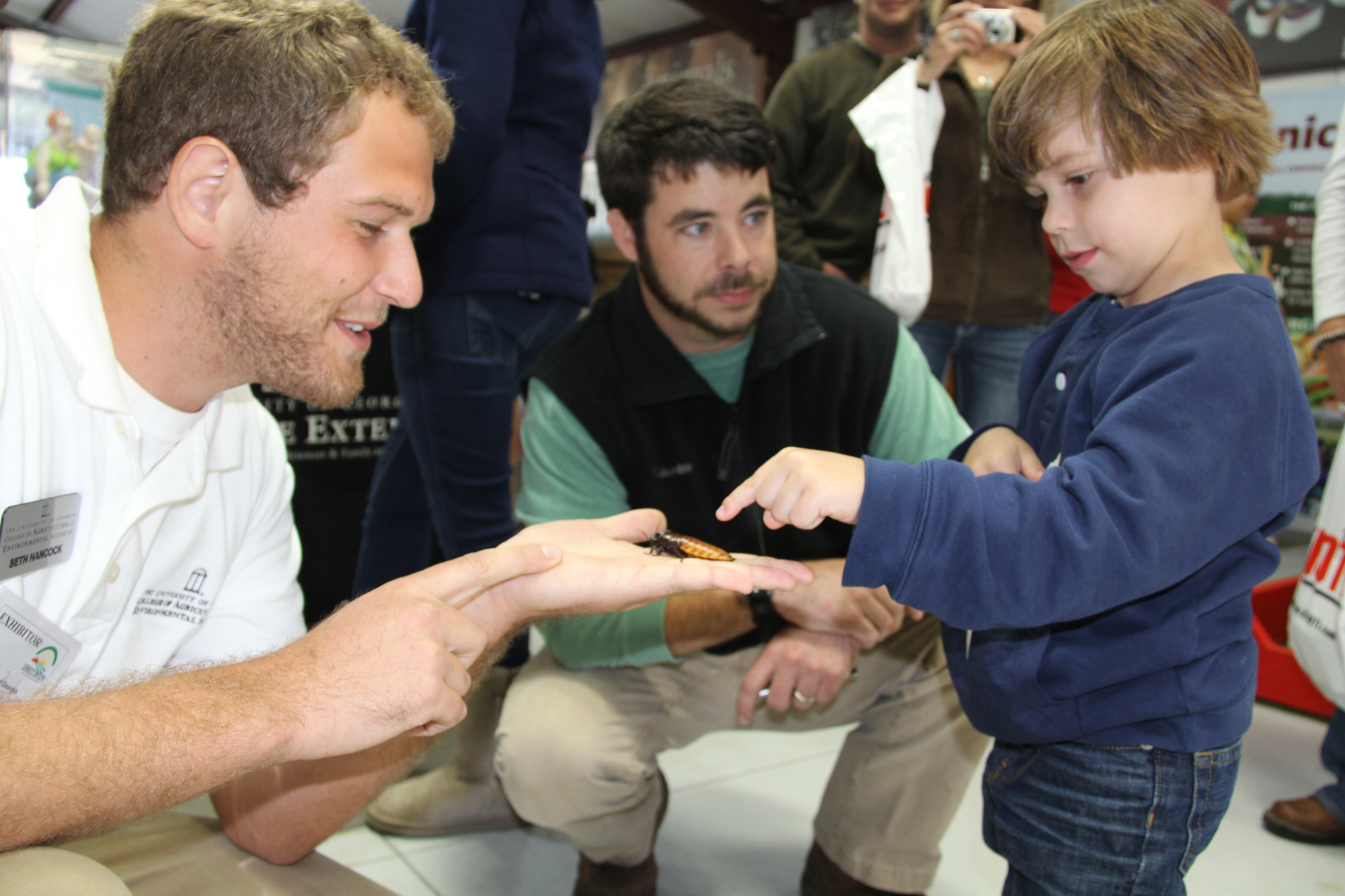 A young visitor to the UGA Pavilion at the 2011 Sunbelt Ag Expo in Moultrie, Ga., Oct. 19 learns about giant cockroaches.