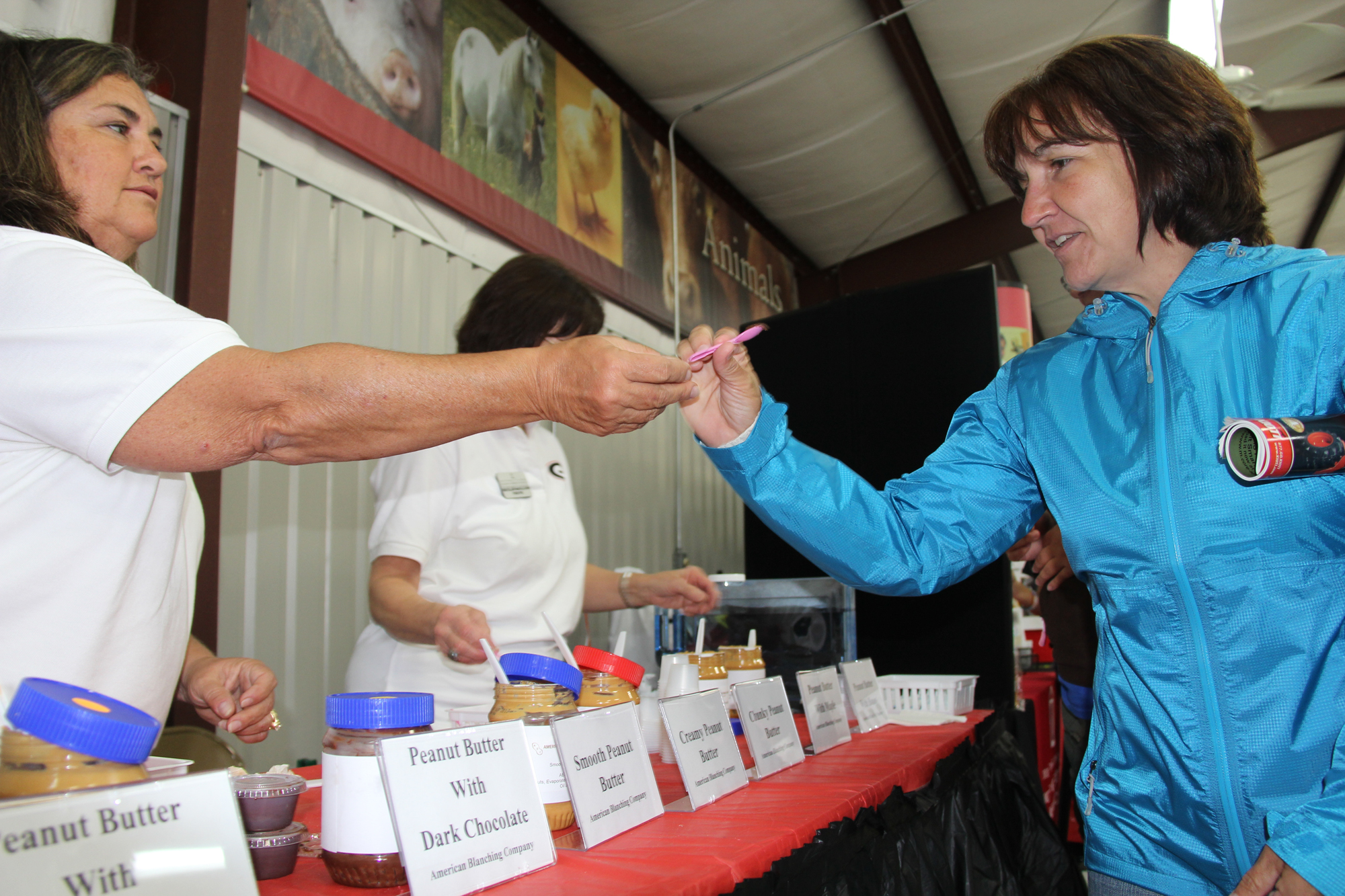 A visitor to the UGA Pavilion at the 2011 Sunbelt Ag Expo in Moultrie, Ga., Oct. 19 takes a sample of the many flavors offered at this year's Expo.