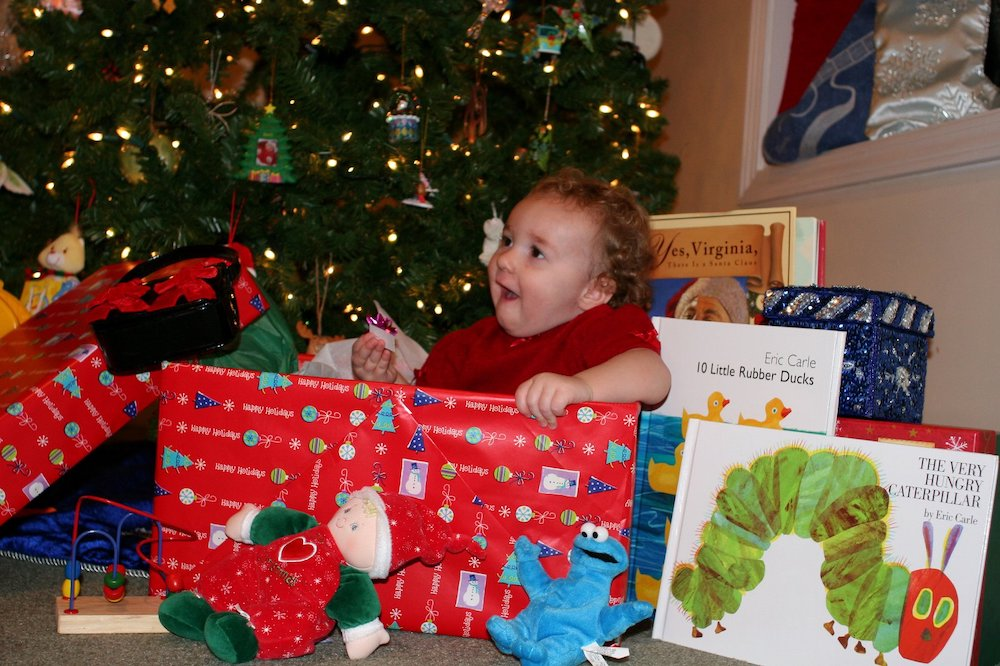 A toddler sits under a Christmas tree surrounded by presents