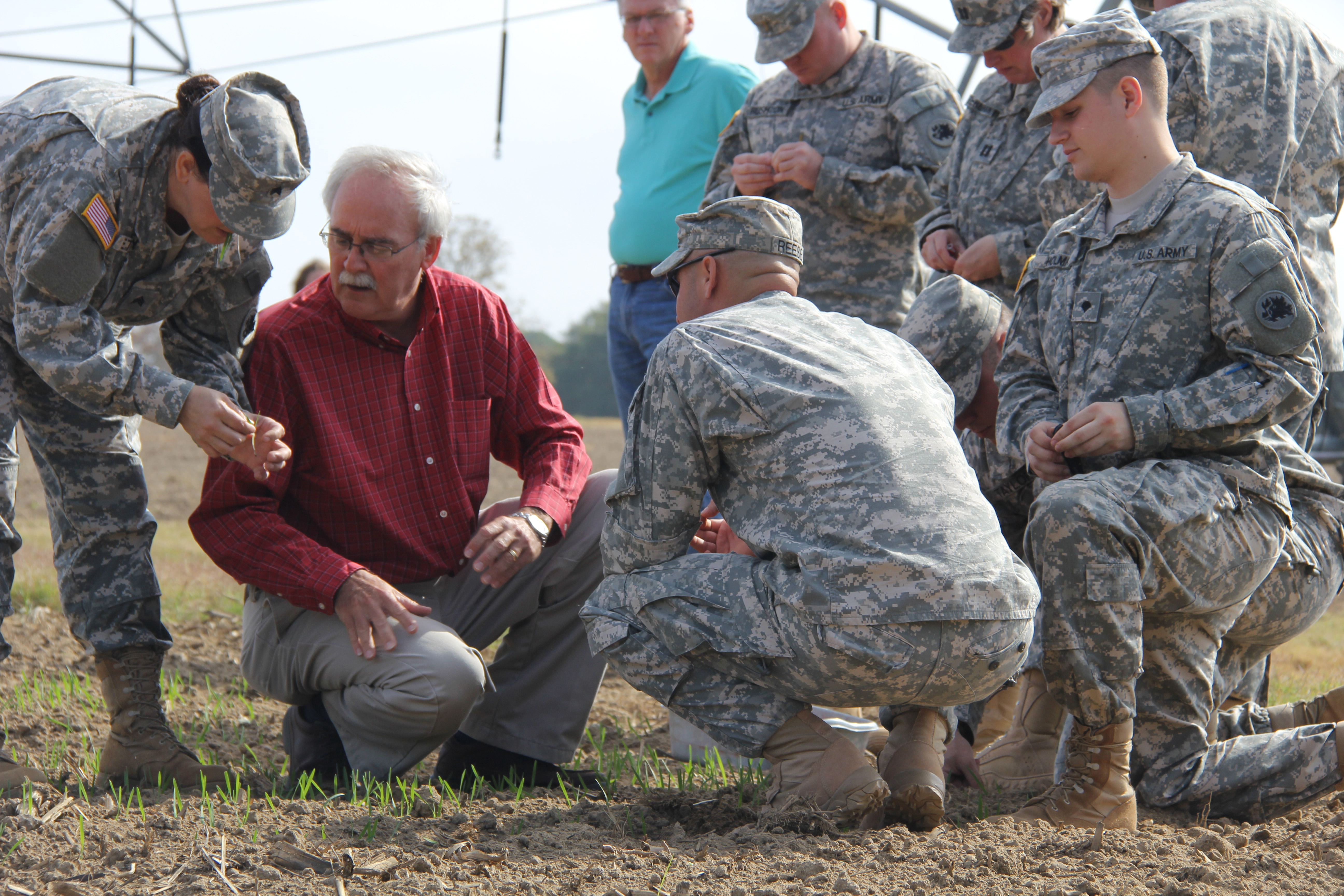 Dewey Long shows newly planted wheat to members of the Georgia National Guard. In Afghnistan, wheat is a vital crop for the population providing food and shelter for the people and animals.