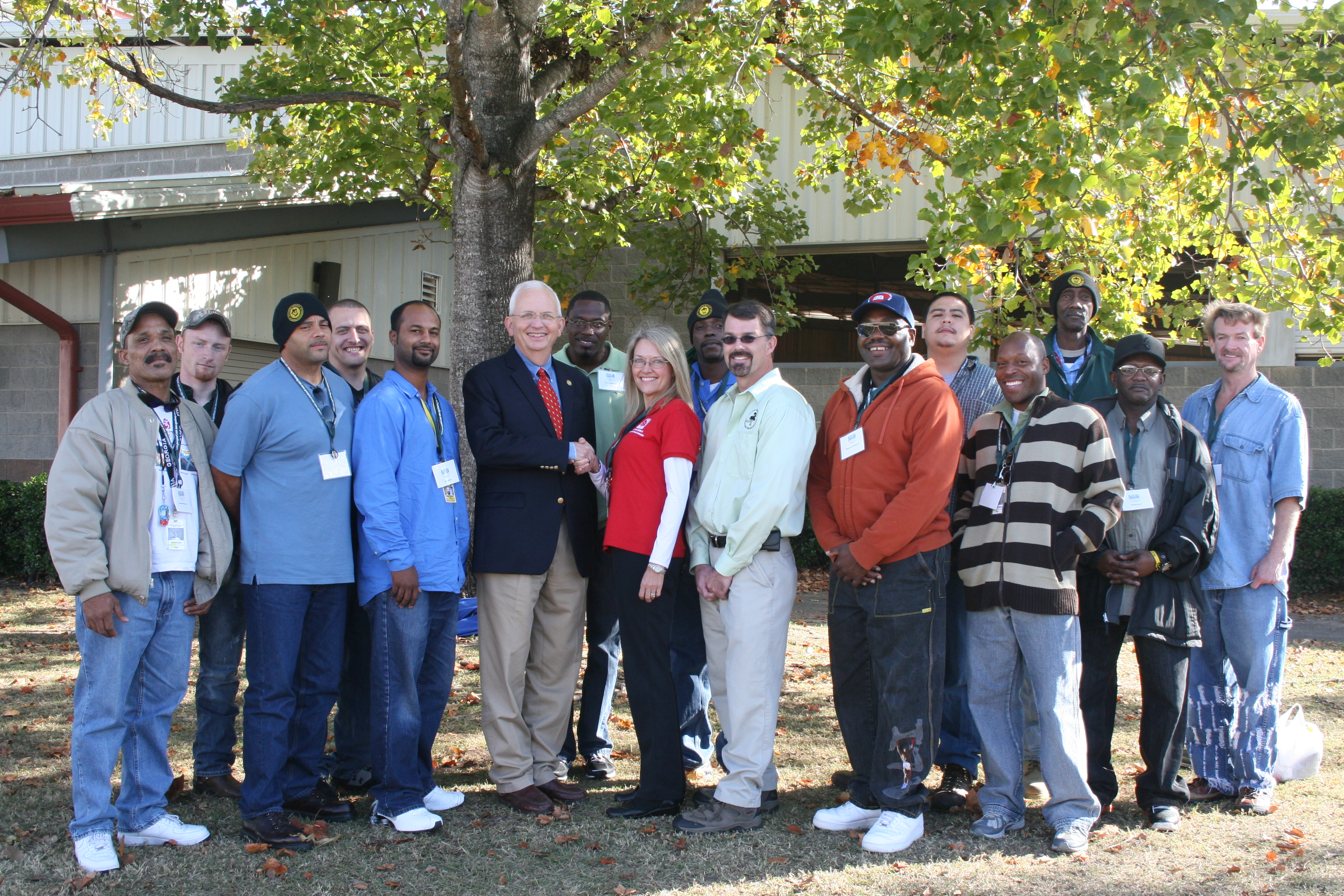 A group of clients from the Atlanta Mission recently graduated from landscaping classes offered by University of Georgia Extension.  Georgia Commissioner of Agriculture Gary Black (center in blue blazer) is shown congratulating the men and their instructor Louise Estrabrook (red shirt), UGA Extension agent in Fulton County.