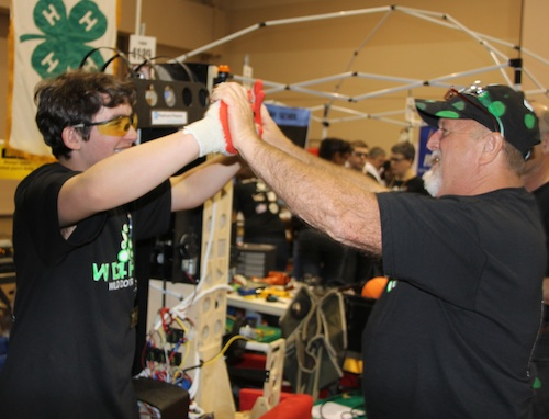 4-H'er Tristan Gaskins and his father/coach Bob Gaskins do a double high five after their robot fares well in competition.