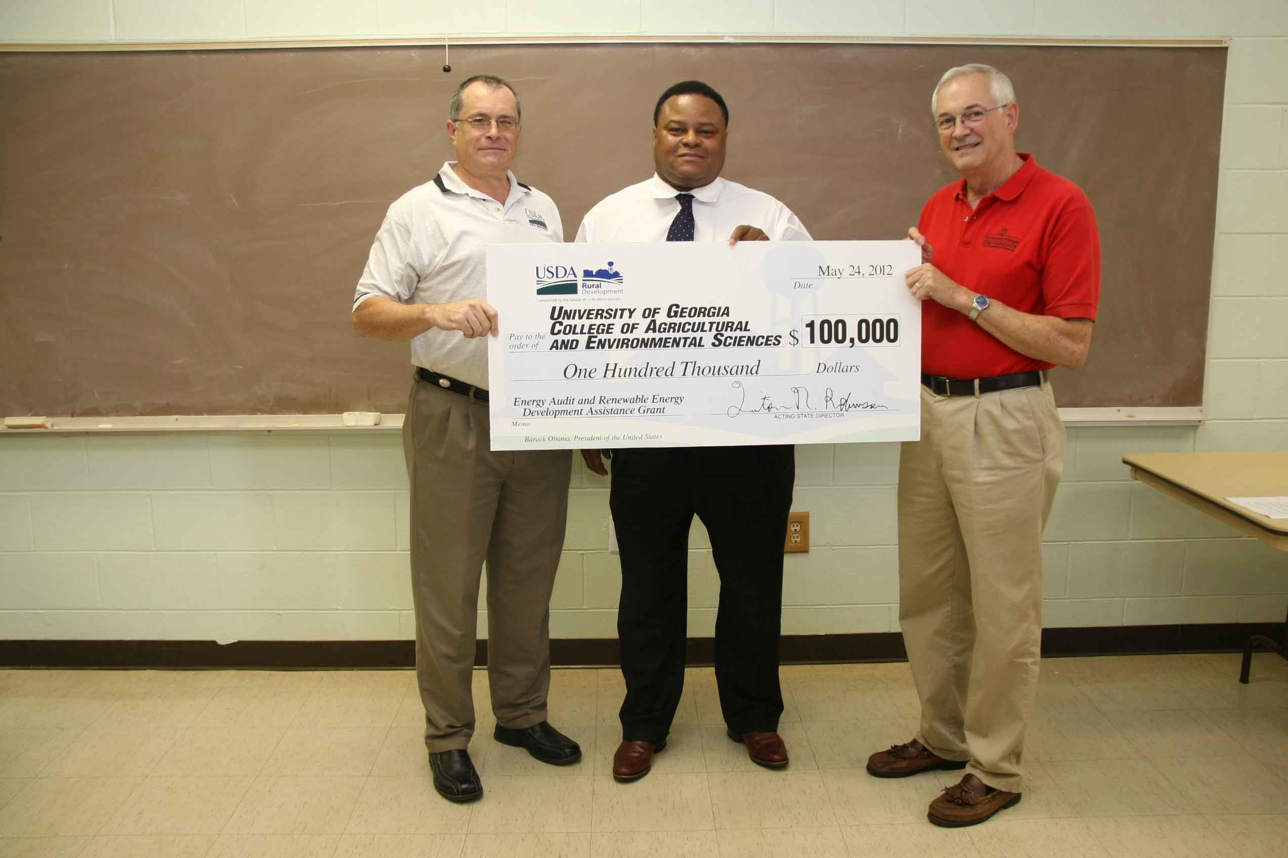 Craig Scroggs, USDA's rural Renewable Energy Coordinator, and  Quinton Robinson, director of USDA Rural Development for Georgia present Associate Professor John Worley with a $100,000 grant.  Worley, an Extension engineer with the UGA College of Agricultural and Environmental Sciences, will use the money to help conduct energy audits of farms in Georgia.
