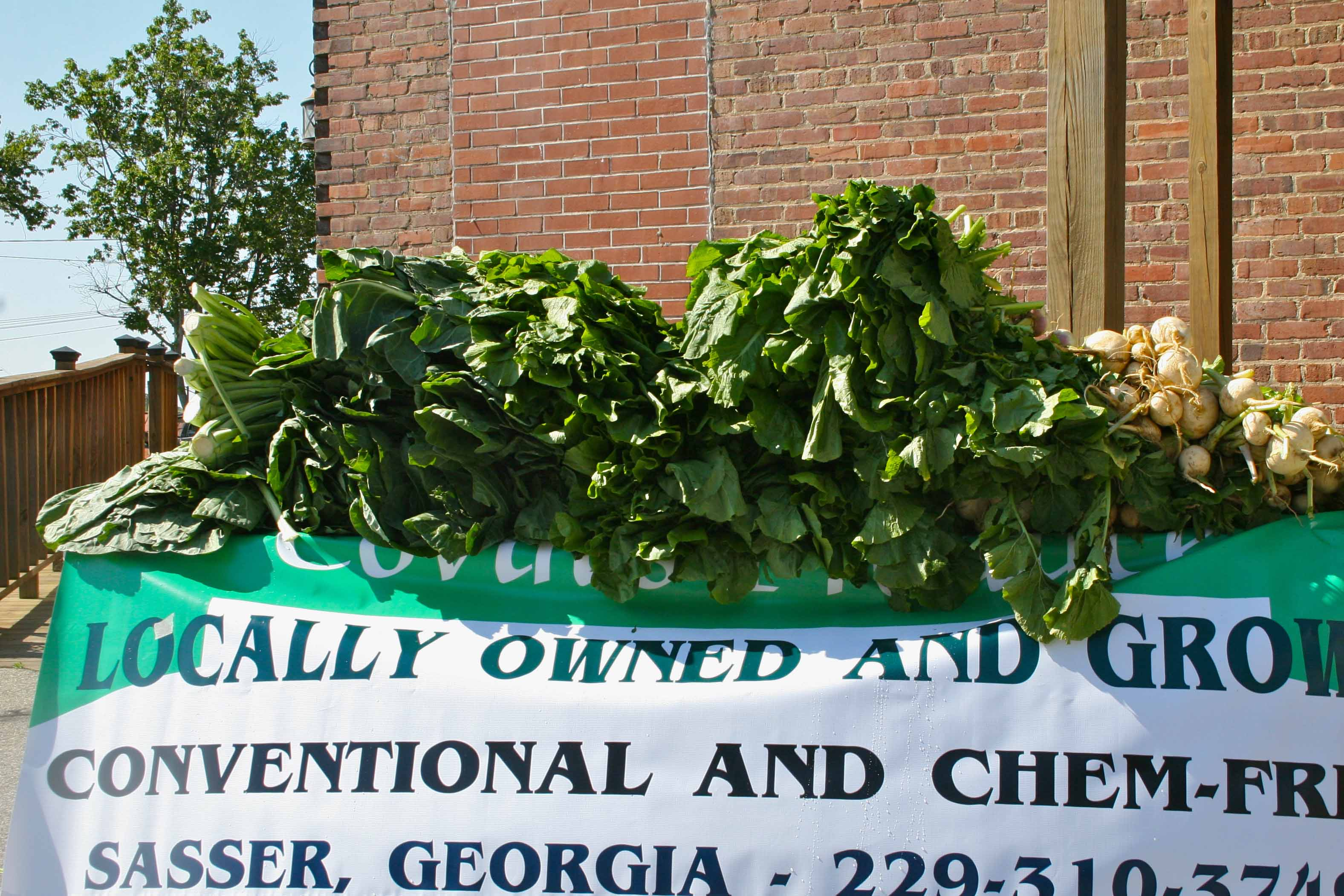 A market stand selling greens at the downtown farmers market in Tifton, Ga.