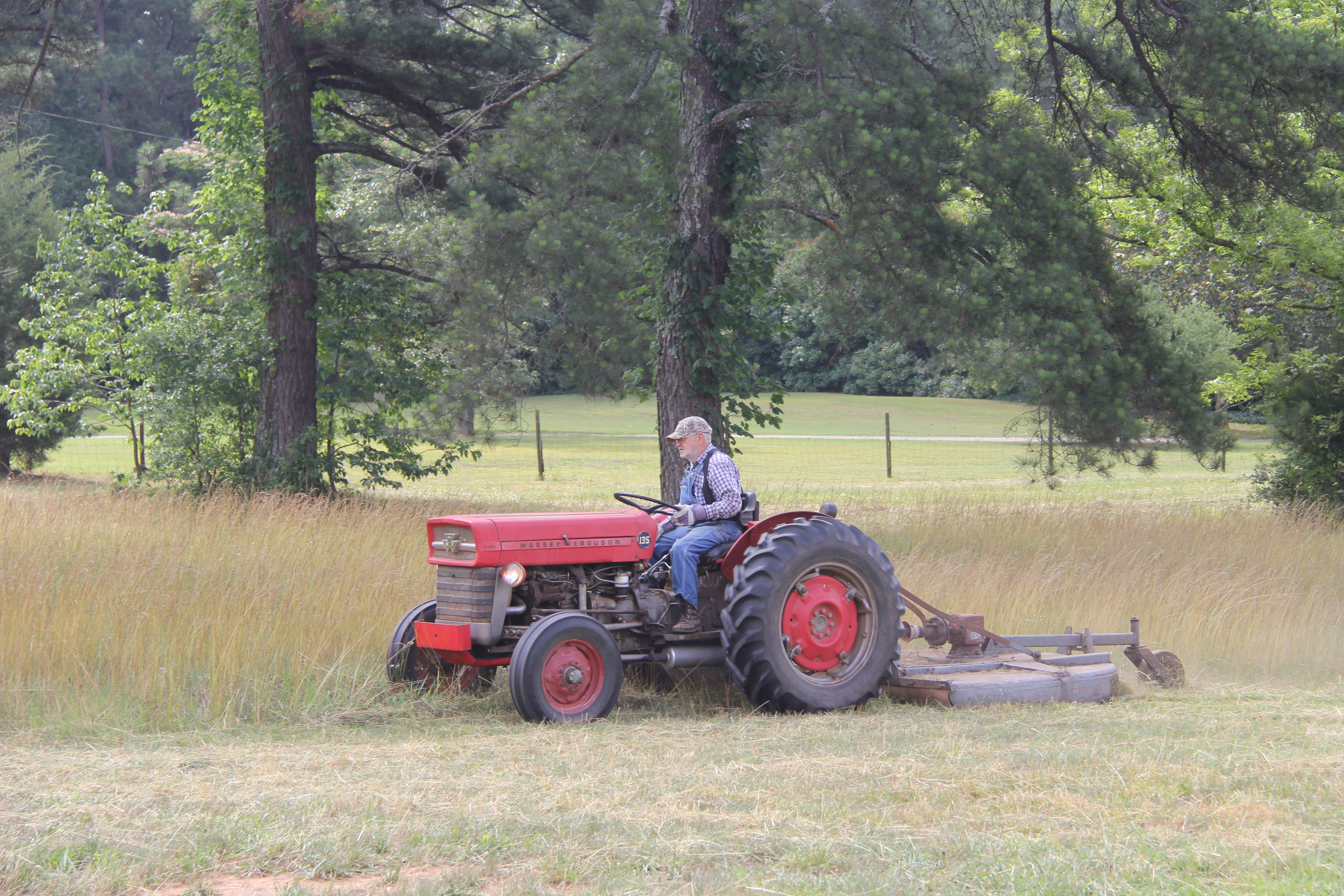 Small farmer James Cobb mows a field in Butts County, Ga.